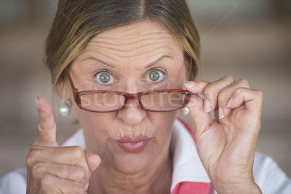 Mérges elegáns nő szemüveg mutat ujj Stock fotó © roboriginal
