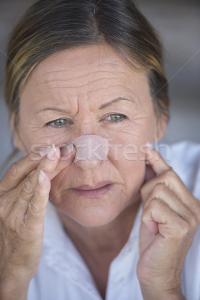 Stressed woman with band aid on injured nose Stock photo © roboriginal