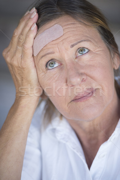 Woman in pain and band aid on forehead Stock photo © roboriginal
