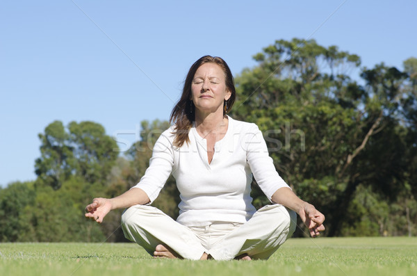 Relaxed yoga meditating mature woman Stock photo © roboriginal