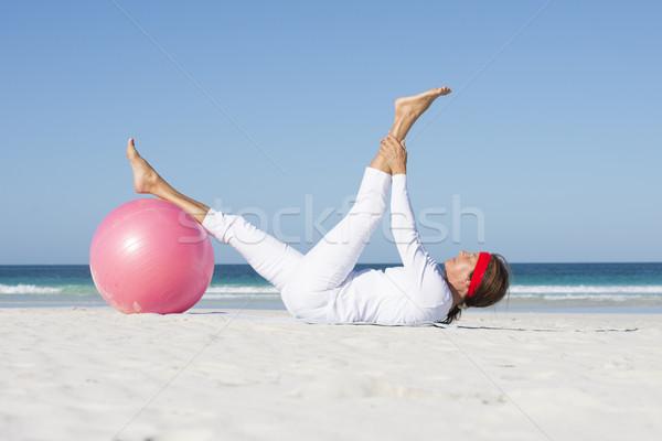 Sporty Mature woman exercising beach Stock photo © roboriginal