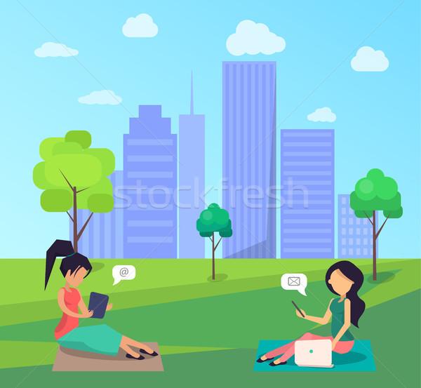 Dwie kobiety posiedzenia trawnik centralny miasta parku Zdjęcia stock © robuart