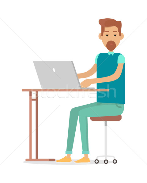 Man with Beard Sitting at Desk Working on Notebook Stock photo © robuart