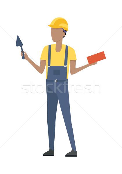 Builder in Helmet and Blue Uniform. Brick. Trowel Stock photo © robuart