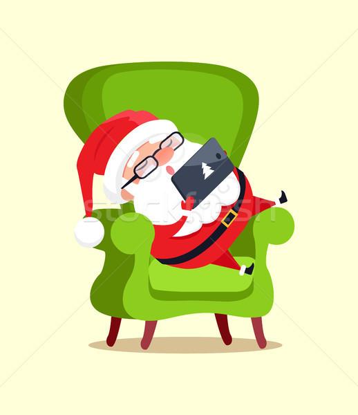 Święty mikołaj siedzieć duży fotel nowoczesne tabletka Zdjęcia stock © robuart