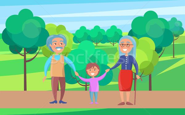 Heureux grands-parents couple de personnes âgées marche petit-fils mains tenant Photo stock © robuart