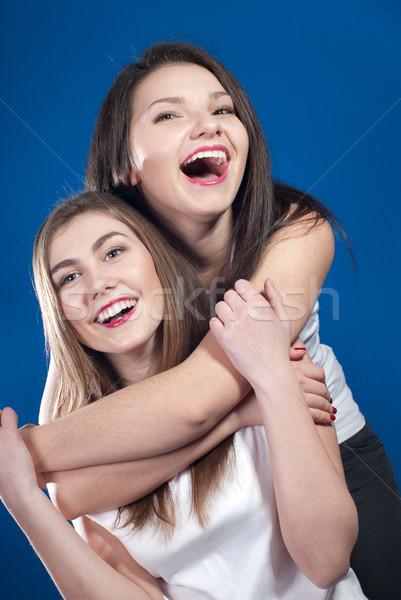 Kettő fiatal boldog nők kék képernyő Stock fotó © rosipro