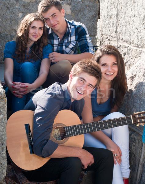 Boldog négy tinédzserek ül együtt lépcső Stock fotó © rosipro