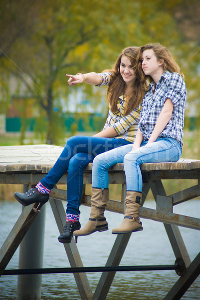 Two school girls sitting on river bridge Stock photo © rosipro