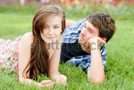 Happy young couple in love lying on green grass Stock photo © rosipro