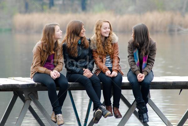 Four school girls sitting on river bridge Stock photo © rosipro