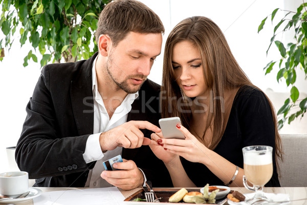 Young couple paying for ther order at the restaurant Stock photo © RossHelen