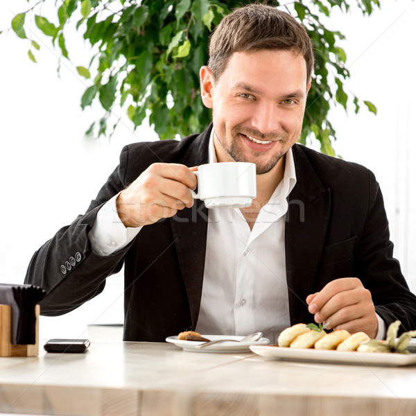 Handsome man drinking coffee at the restaurant Stock photo © RossHelen