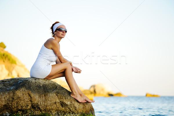 Nő ül kő tenger gyönyörű nő néz Stock fotó © rozbyshaka