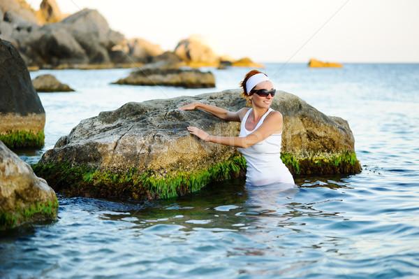 Gyönyörű nő csobbanás tenger kövek égbolt lány Stock fotó © rozbyshaka