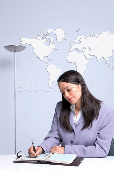 Businesswoman sat at her office desk writing Stock photo © RTimages