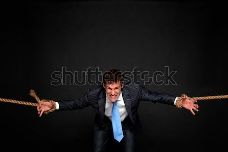 Businessman being pulled by rope on both sides. Stock photo © RTimages