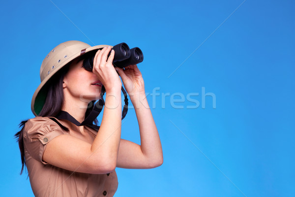 Woman in safari hat searching with binoculars Stock photo © RTimages