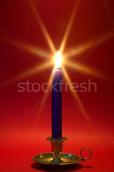 Blue candle in brass holder on red. Stock photo © RTimages