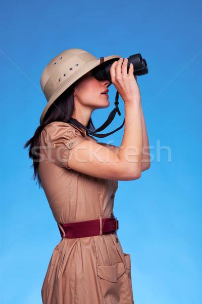 Woman in safari hat looking through binoculars side view Stock photo © RTimages