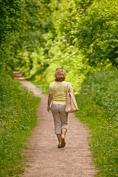 Woman walking down a footpath on a sunny day. Stock photo © RTimages