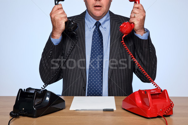 Businessman sat at desk with two telephones. Stock photo © RTimages