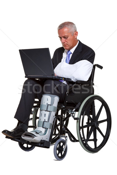 Injured businessman on laptop in a wheelchair isolated Stock photo © RTimages
