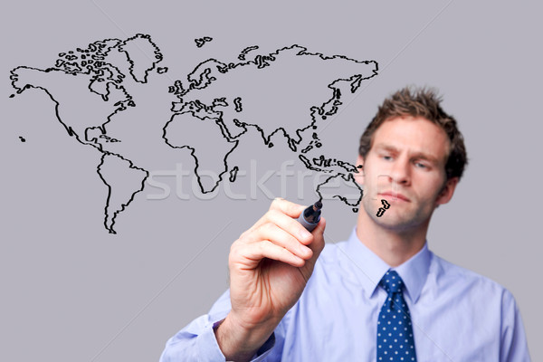 Stock photo: Businessman drawing the world map on a glass screen.
