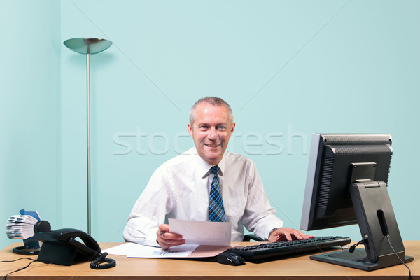 Mature businessman sat at his office desk Stock photo © RTimages