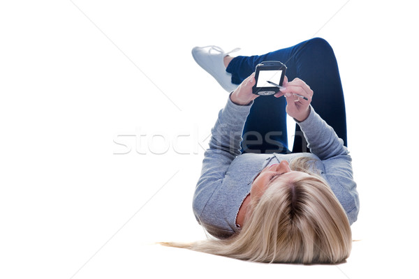 Woman lying down writing on her pda isolated Stock photo © RTimages