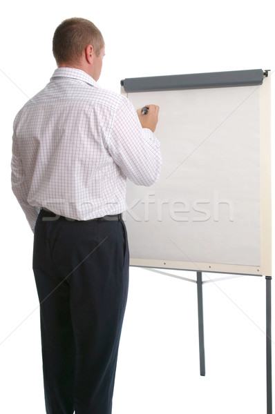 Businessman writing on a flip chart.  Stock photo © RTimages