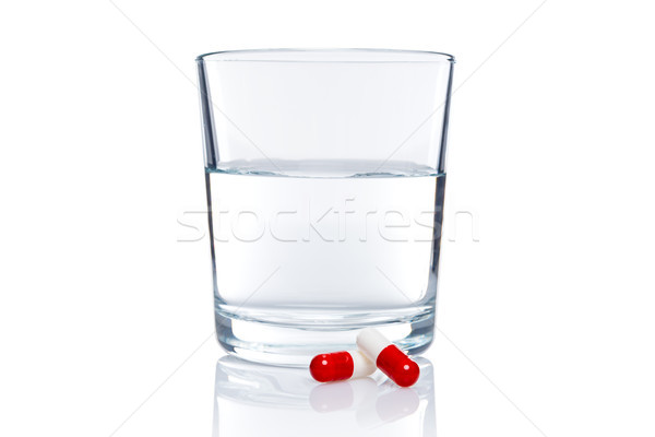 Glass of water and two pills isolated on white Stock photo © RTimages