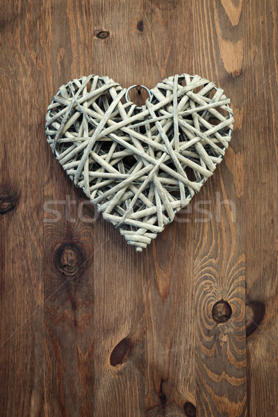 Reed heart hanging against a rustic wooden background. Stock photo © RTimages