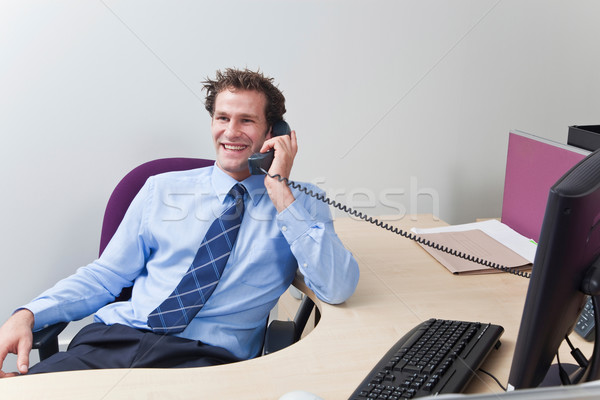 Businessman sat at his desk talking on the telephone. Stock photo © RTimages
