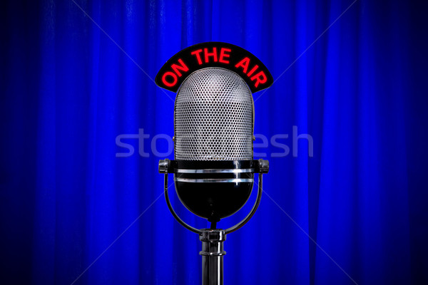 Microphone on stage with spotlight on blue curtain Stock photo © RTimages