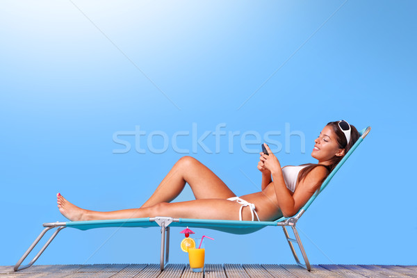 Woman sunbathing and reading her text messages Stock photo © RTimages