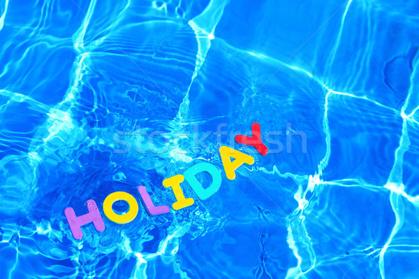 Word HOLIDAY floating in a swimming pool Stock photo © RTimages