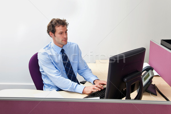 Male office worker sat working at his desk Stock photo © RTimages
