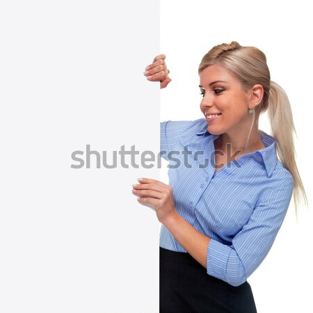 Stock photo: Blond woman holding the side of a blank sign board.
