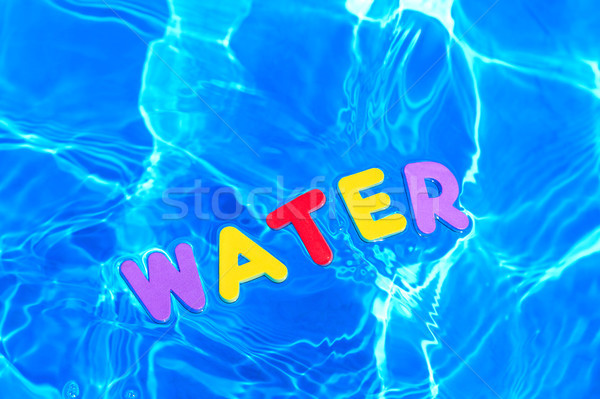 Word WATER floating in a swimming pool Stock photo © RTimages