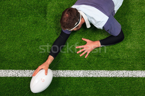 Stock photo: Rugby player scoring a try with one hand on the ball