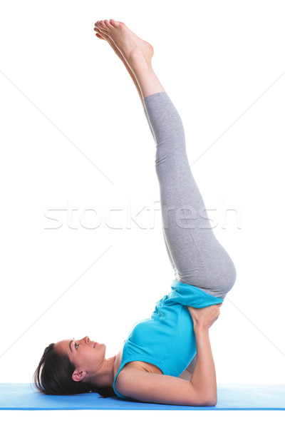 Woman doing yoga shoulder stand Stock photo © RTimages