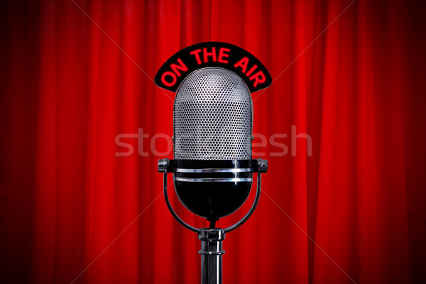 Microphone on stage with spotlight on red curtain Stock photo © RTimages
