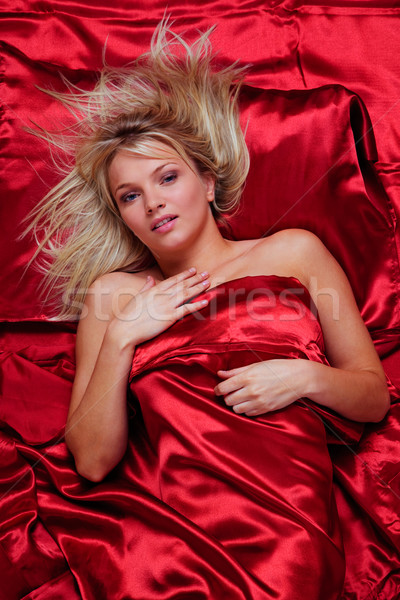 Beautiful blonde woman in a bed of red silk sheets Stock photo © RTimages