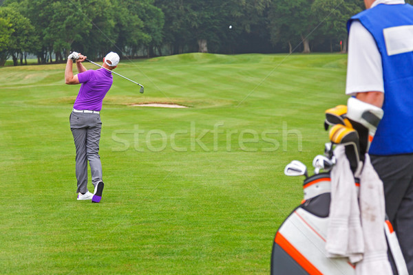 Pro golfer playing a shot with caddy Stock photo © RTimages