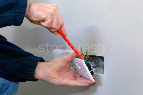 Stock photo: Electrician installing a socket