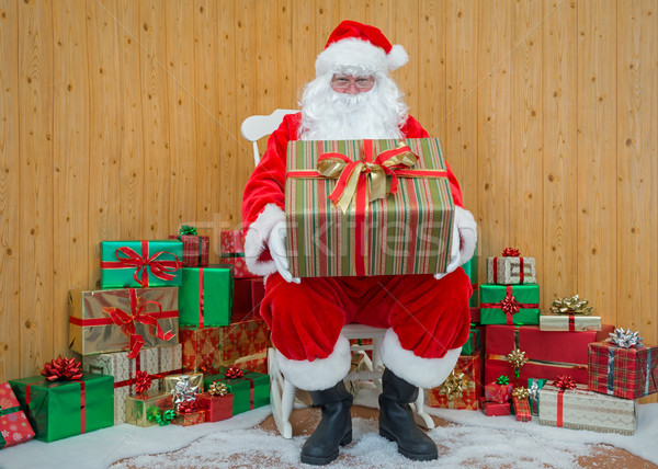 Santa Claus in his grotto holding a gift wrapped present Stock photo © RTimages