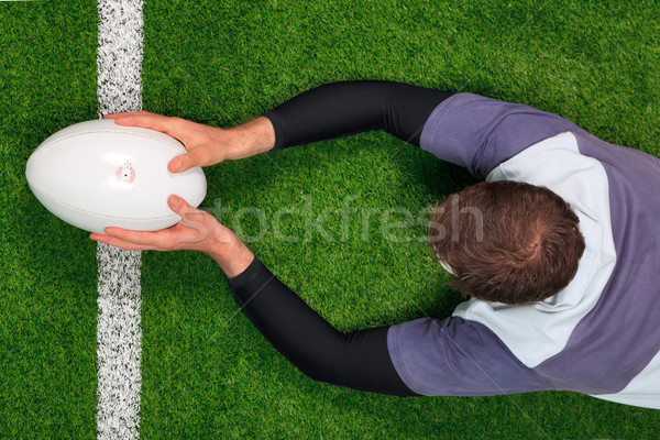 Stock photo: Rugby player scoring a try with both hands.