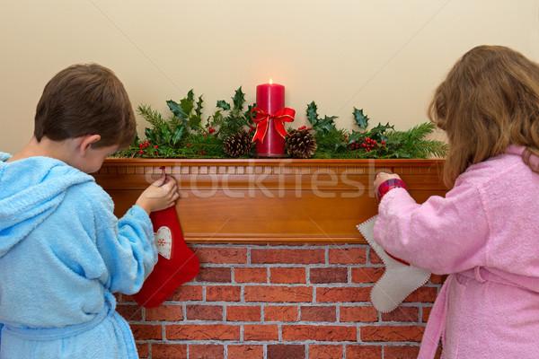 Children hanging stockings over the fireplace Stock photo © RTimages