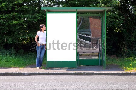 Woman sat at a bus stop next to blank billboard Stock photo © RTimages